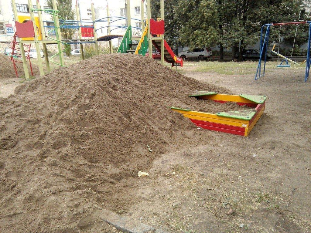 Детская песочница засыпана песком.