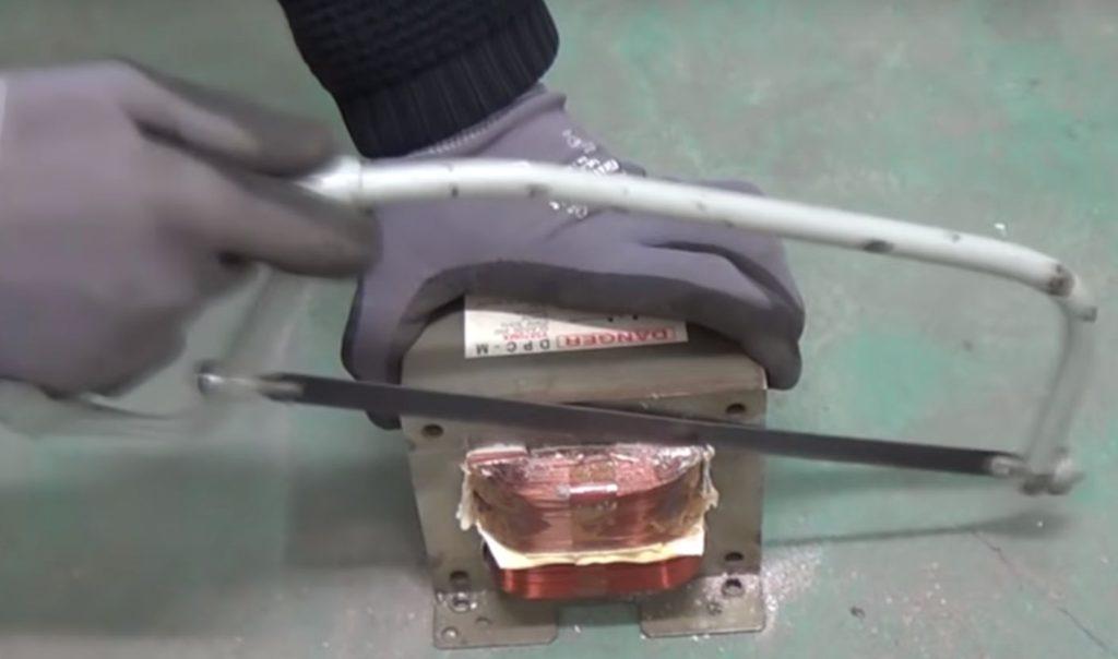 Удаление вторичной обмотки трансформатора с помощью ножовки по металлу.