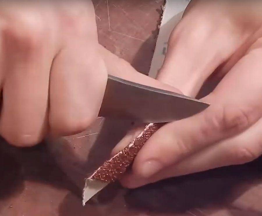 Соскабливаем часть абразива ножом со сгиба ленты.