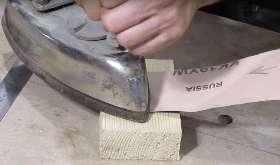 Приклеиваем шлифовальную ленту к деревянной доске и прогреваем место склейки утюгом.