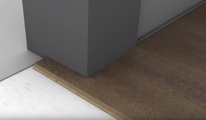 Подрезанная рама двери и уложенный ламинат.