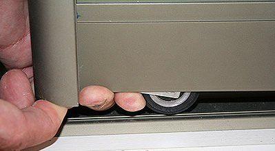 Прижимаем нижний ролик и устанавливаем дверь на место.