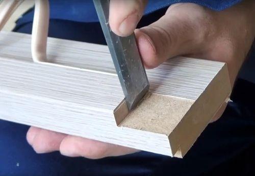 Канцелярским ножом или стамеской срезаем часть материала с верхней планки коробки двери.