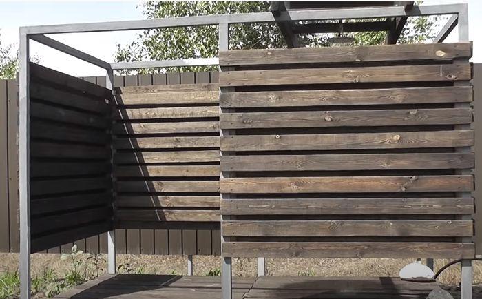Летний душ с металлическим каркасом и обшивкой стен из дерева.