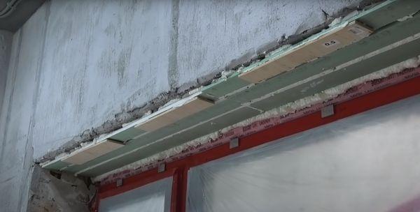 На фото видно остатки от листов гипсокартона и куски фанерного листа, наклеенные на верхний откос.