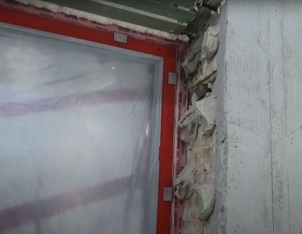 Накидываем клей на стену с помощью шпателя.